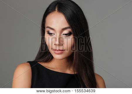 Close up portrait of an attractive young brunette woman with bright make up looking away isolated on a gray background