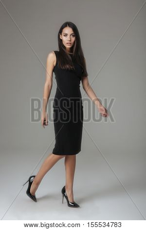 Full length portrait of a young attractive woman posing in black dress isolated on a gray background