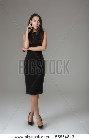 Full length portrait of a beautiful stylish woman in black dress standing and posing isolated on a gray background
