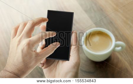 Hand using smart phone with cup of coffee on a wooden table on the background