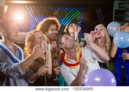 Group of smiling friends blowing party horn in bar