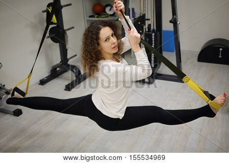 Pretty woman does exercises of Fly Stretching in gym with fitness equipment