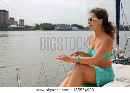 Woman in sunglasses sits on yacht and looks away during sailing at summer