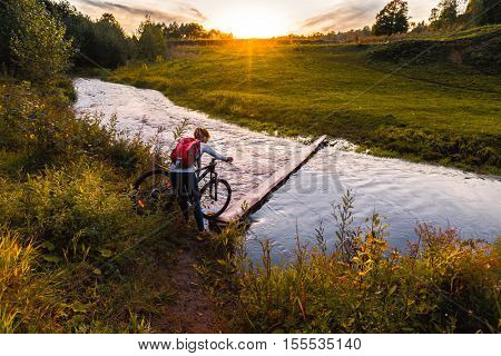 Lady with bicycle crossing the river by wood small bridge