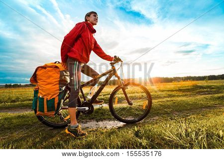 Young lady hiker with loaded bicycle standing on a wet rural road in the meadow