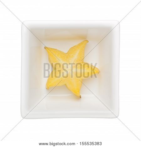 Slice of starfruit in a square bowl isolated on white background