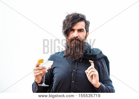 handsome bearded man with stylish hair mustache and beard on serious face in fashion shirt and jacket thrown over shoulder holding glass of alcoholic beverage isolated on white
