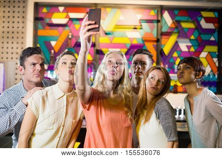 Group of smiling friends taking a selfie from mobile phone in bar