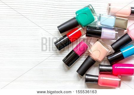lot of bottles of nail polish on wooden background top view