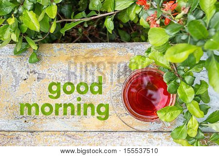 Glass cup of tea on a wooden surface, green grass around. Red orange flowers. Text Good morning on the background.