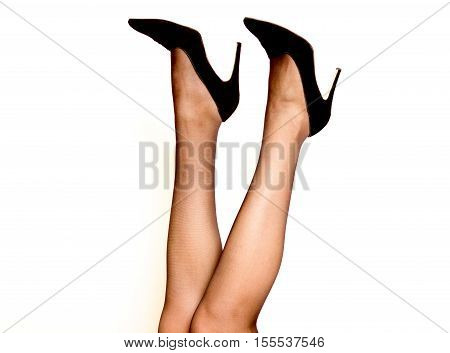 Women's legs in pantyhose and high heels. Black color