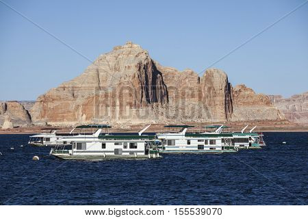 Desert sandstone peaks and houseboats on Lake Powell in the Glen Canyon National Recreation Area.