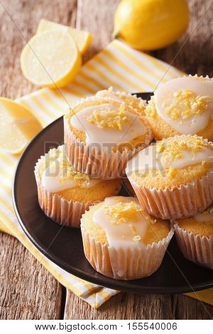 Sweet Lemon Muffins With Zest And Icing Sugar Close-up On A Plate. Vertical