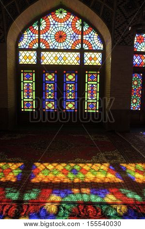 IRAN PINK MOSQUE Shiraz 2016 - Persian Nasir-ol-Molk Mosque in Shiraz Iran at Gowad-e-Araban district with colored glass facade with light reflection on the carpet through colored window
