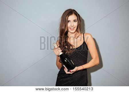 Model with champagne. looking at the camera. in black dress