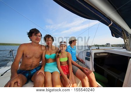 Happy mother, father, daughter and son sail on yacht on river at summer day