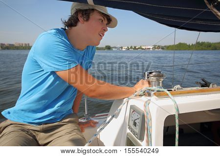 Boy teenager in cap sails on yacht on river at summer sunny day