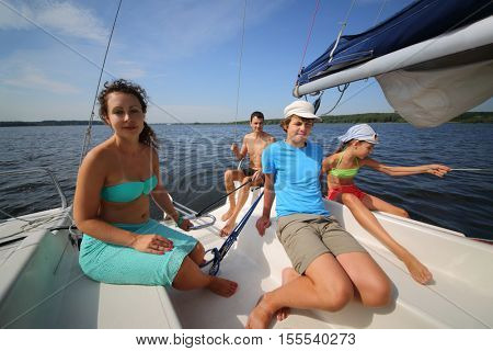 Father, mother, son and daughter sail on white yacht on river at summer sunny day