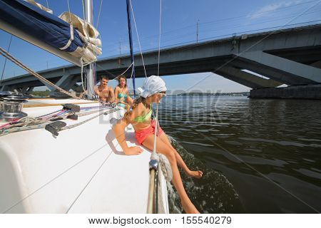 Father, mother and daughter sail on yacht on river under bridge at summer, focus on child