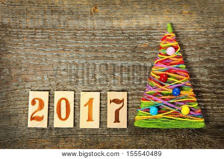 Handmade knitted Christmas tree with numbers 2017 on old wooden background