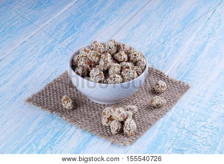 Caramel Coated Peanut with Sesame in blue Wooden Background. Eastern dessert