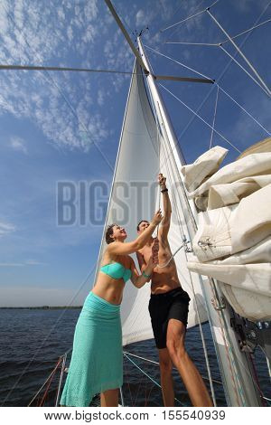 Man and woman set sail of white yacht on river at summer sunny day
