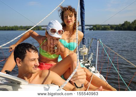 Father, mother and daughter sail on yacht on river at sunny summer day, focus on man