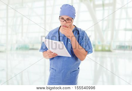 worried doctor looking to his notes at the hospital