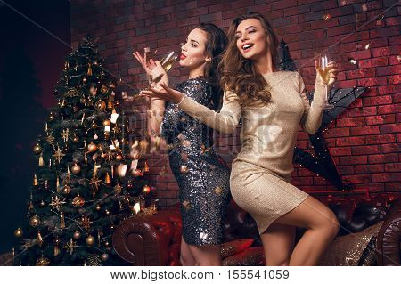 Portrait Of Two Smiling Girl With Tinsel Confetti In Hands And Wineglasses With Champagne