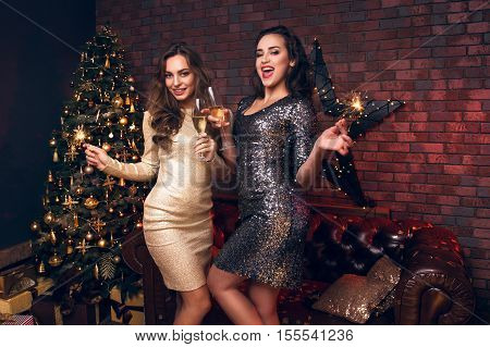 Two Elegant Girl In A Gold Dress Happy To Christmas. Girls Dancing And Smiling Near For Christmas Tr