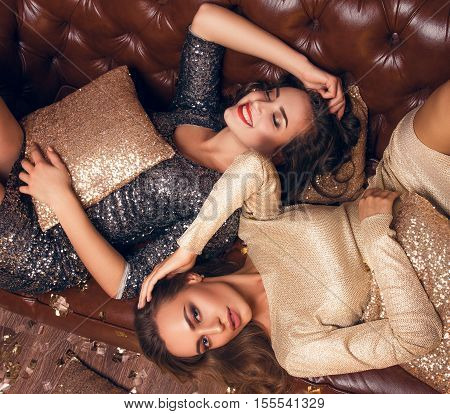 Two  Girls Lie On The Bed And Smiling. After Christmas Party.