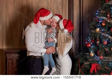 Young family with  little son stand near Christmas tree in the room. Merry Christmas and Happy New Year.