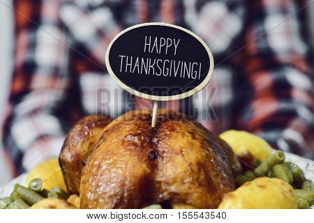 closeup of a young caucasian man carrying a tray with a roast turkey topped with a black signboard with the text happy thanksgiving written in it