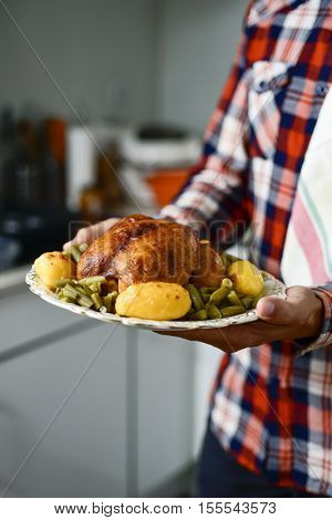 closeup of a young caucasian man carrying a ceramic tray with a roast turkey served with potatoes and french beans, in his kitchen