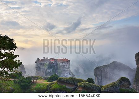 Meteora monasteries. Beautiful view on the Holy Monastery of Varlaam placed on the edge of high rock covered of the morning clouds and mist at sunrise Kastraki Greece. Roussanou monastery on background