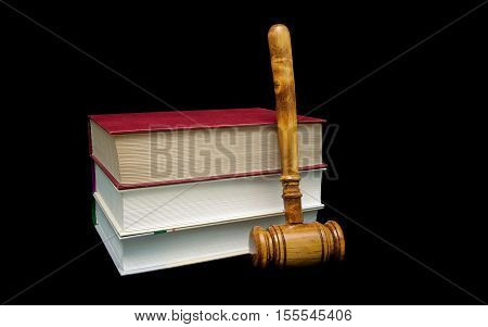 books and a wooden judge's gavel on a black background. horizontal photo.