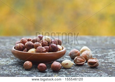Hazelnut kernels and whole hazelnuts on old rustic table. Autumn concept.