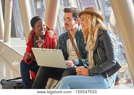 3 Young Adults Entrepreneurs Or Students Group Mixed Race Around Laptop Having A Discussion