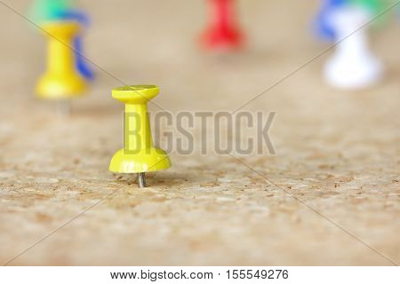 Closeup image of a yellow pushpin resting in a cork board.