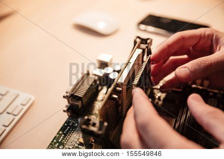 Closeup of man hands installing microprocessor into motherboard on the table