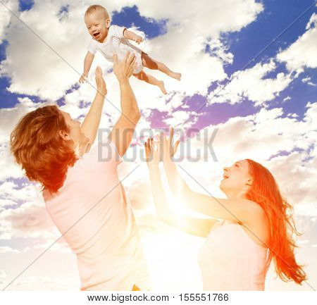 Happy family throws up baby boy against blue sky and white clouds