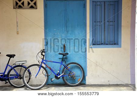 Bicycle leaning against a white painted brick wall