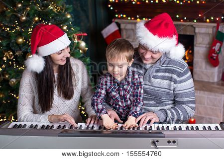 Family - mother father and kid wearing santa hats playing the piano over festival christmas background
