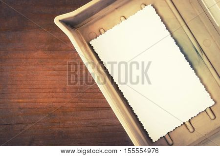 A cell with photo paper on the table in the old darkroom