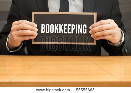 Bookkeeping. word writing on black banner and holding by businessman