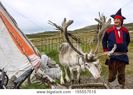 Honningsvag, Norway - Sep 3, 2016: Deer and reindeer breeder dressed in national clothes the Sami in the area of town Honningsvag. The Sami are the people inhabiting the Arctic area.