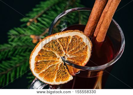 Mulled wine in irish glass decorated with dried orange slices. Details over black background. Selective focus