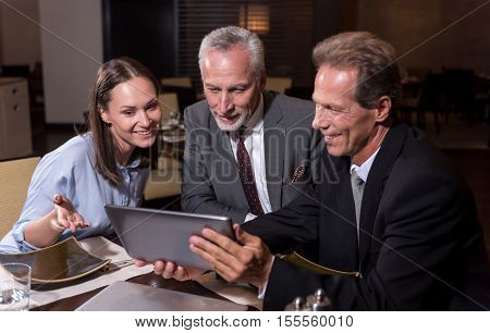 Enjoyable process of sharing opinions. Pleasant smiling involved colleagues sitting at the table and working with the tablet while expressing interest and sharing ideas in the restaurant