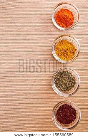 Many different spices in glass jars, and a special seasoning for pilaf. aromatic seasoning for cooking in the kitchen. View from above