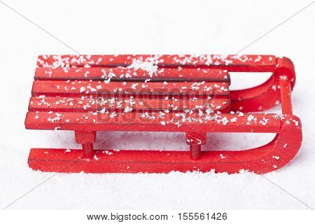 Wooden red sled with snow isolated on white background